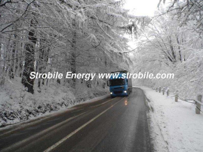 Un camion di Virgin Wood Pellets Abete Bianco si sta precipitando attraverso le foreste invernali della Bucovina per i consumatori al dettaglio